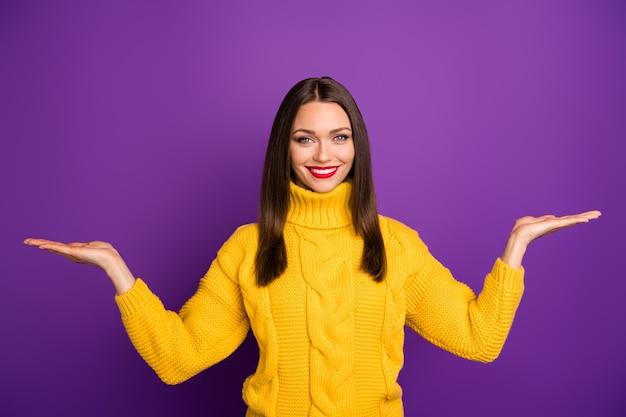Портрет жизнерадостной позитивной милой привлекательной женщины, держащей две вещи руками, зубастой улыбкой, держащей пустое пространство.