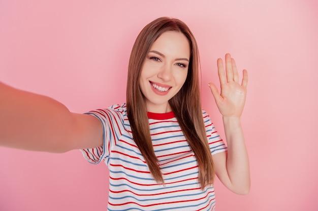 陽気なポジティブフレンドリーな女性の肖像画はピンクの背景にselfie波の手を撃ちます