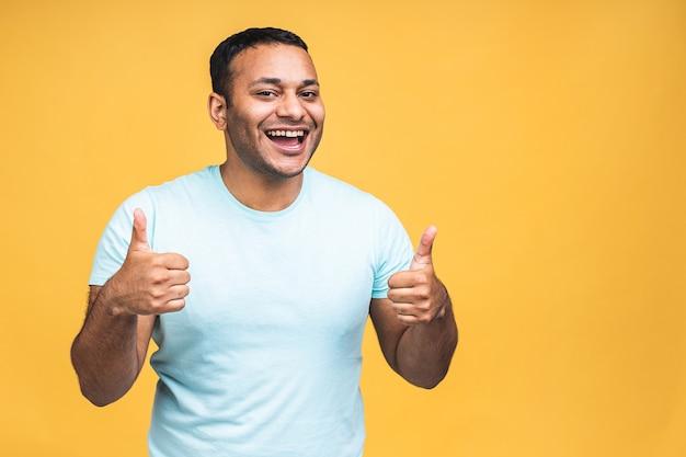 陽気な、前向きな、ハンサムなアフリカ系アメリカ人のインドの黒人男性の肖像画、黄色の背景に分離されたカメラに指で親指を見せてカジュアルに笑顔を輝かせます。