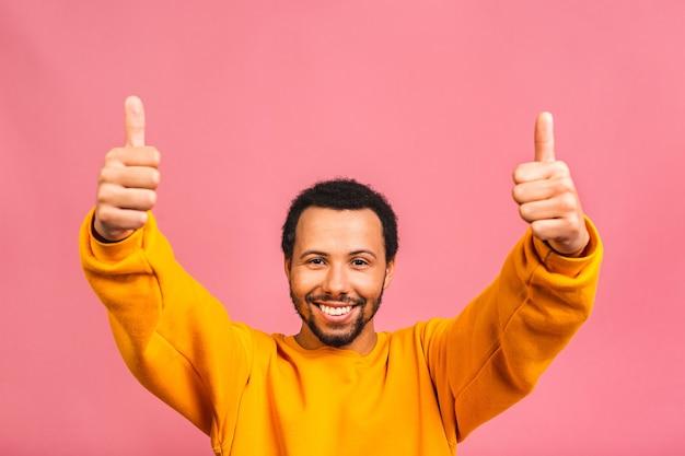 쾌활하고 긍정적 인 잘 생긴 남자, 분홍색에 고립 된 카메라에 손가락으로 엄지 손가락을 보여주는 캐주얼에 빛나는 미소의 초상화.