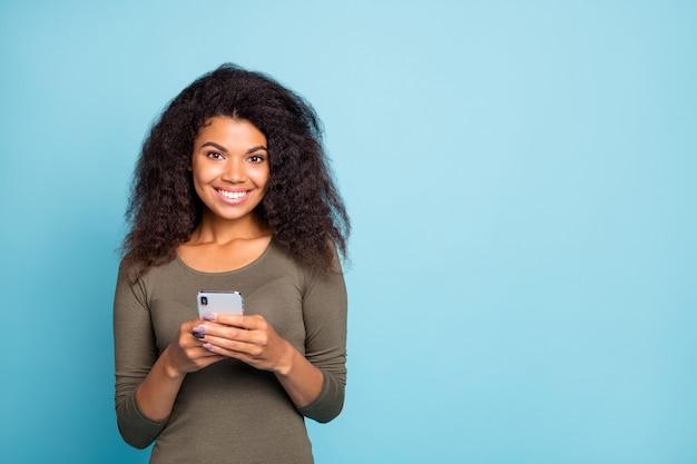 Портрет веселой позитивной милой девушки-мулатки использует свой смартфон типа текстовых комментариев в учетной записи социальной сети блога носить одежду повседневного стиля, изолированную на синей стене