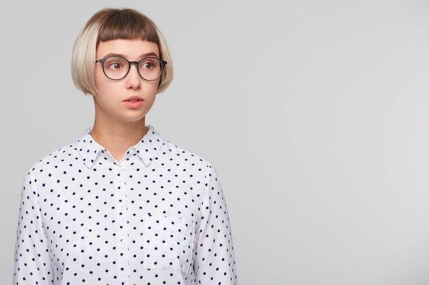 陽気なきれいな金髪の若い女性の肖像画は水玉シャツを着ています