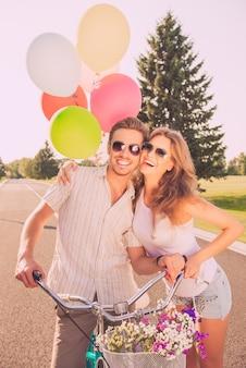 자전거와 풍선 사랑에 쾌활한 예쁜 부부의 초상화