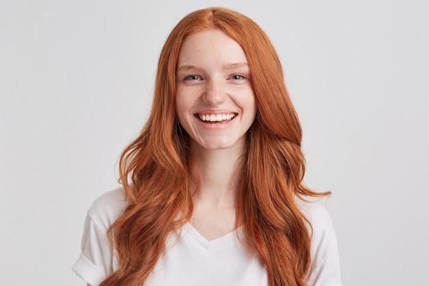 긴 물결 모양의 머리카락과 주근깨를 가진 쾌활한 예쁜 빨간 머리 젊은 여자의 초상화