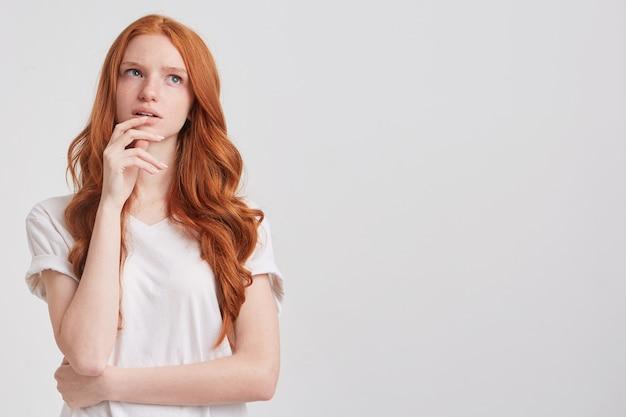 긴 물결 모양의 머리를 가진 명랑 예쁜 빨간 머리 젊은 여자의 초상화