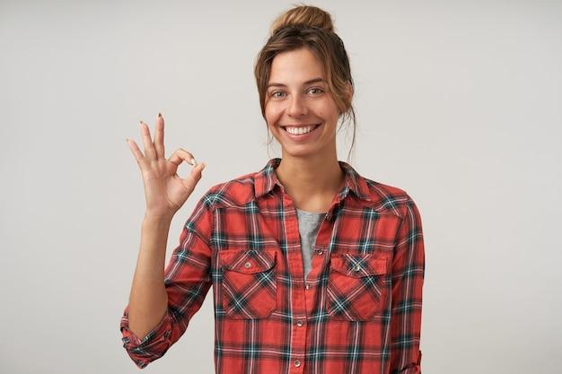 체크 무늬 셔츠에 쾌활한 예쁜 여자의 초상화, 확인 제스처를 보여주는 캐주얼 헤어 스타일, 넓게 웃고, 화이트 포즈
