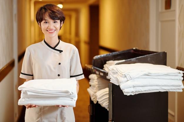 新鮮なふわふわの白いタオルのスタックを保持している陽気なかなり若いベトナムのメイドの肖像画