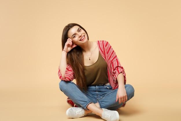 スタジオでパステルベージュの壁の背景に分離されたカメラを見て、座っているカジュアルな服を着た陽気なかなり若い女性の肖像画。人々の誠実な感情、ライフスタイルのコンセプト。コピースペースをモックアップします。