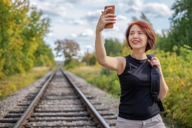 Портрет веселой рыжеволосой молодой женщины в черной футболке и белых джинсах