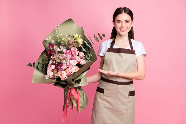 Портрет веселой надежной владелицы магазина девушки, представляющей букет цветов