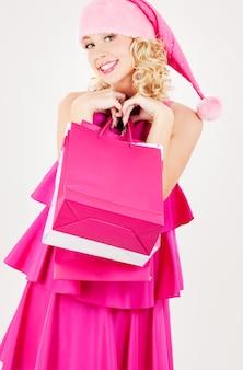 쇼핑백과 쾌활 한 산타 도우미 여자의 초상화