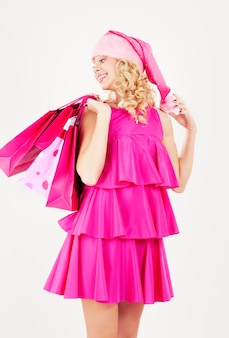 ショッピングバッグと陽気なサンタヘルパーの女の子の肖像画