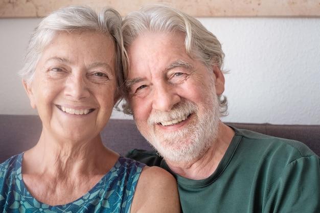 家でリラックスしている年配の幸せなカップルを抱きしめて笑っている陽気な年配のカップルの肖像画