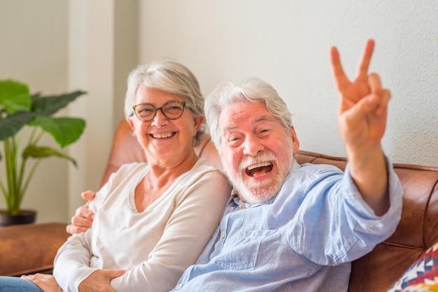 Портрет жизнерадостной пары старших обнимая сидя на софе и смеясь над. пожилая пара счастлива расслабляющий и позирует v знак перед камерой, сидя в гостиной.