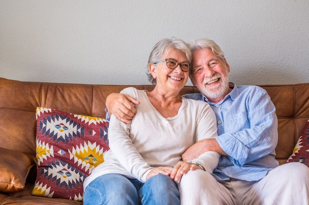 소파에 앉아서 웃으면서 껴안은 쾌활한 수석 부부의 초상화. 노인 행복한 커플은 휴식을 취하고 거실에 앉아 카메라 앞에서 포즈를 취합니다.