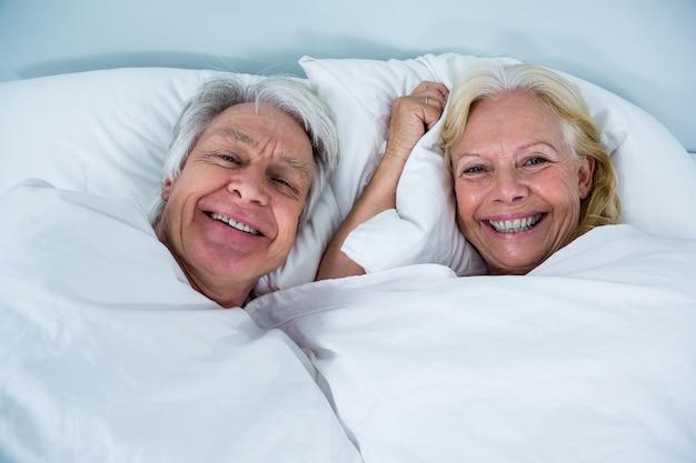 ベッドで寝ている陽気な年配のカップルの肖像画