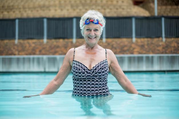 수영장에서 수영하는 쾌활 한 고위 여자의 초상화