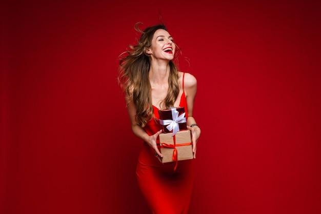 빨간색 실크 드레스를 입고 팔에 두 개의 포장 된 선물을 들고 바람에 긴 갈색 머리를 가진 쾌활한 섹시한 여자의 초상화