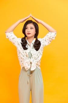 Портрет веселой улыбающейся модной девушки сходит с ума в повседневной хипстерской летней одежде на желтом фоне
