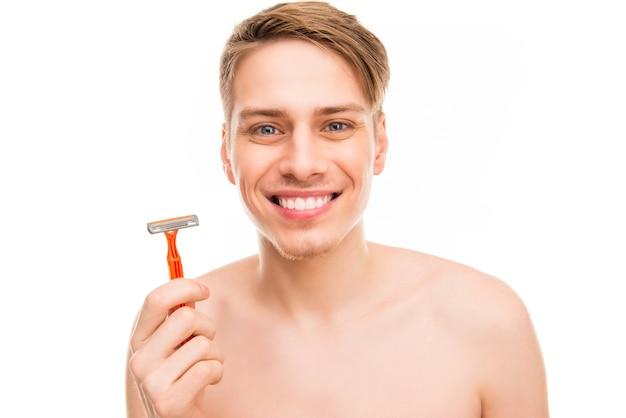 かみそりを持っている陽気な笑顔の健康な男の肖像画