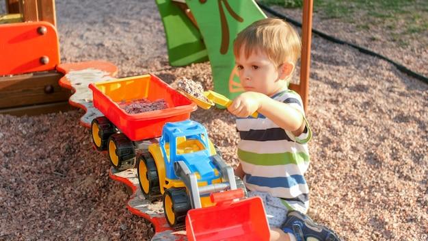 トレーラーとおもちゃのトラックに砂を注ぐ陽気な笑顔の小さな男の子の肖像画。公園の遊び場で遊んでいる子供たち
