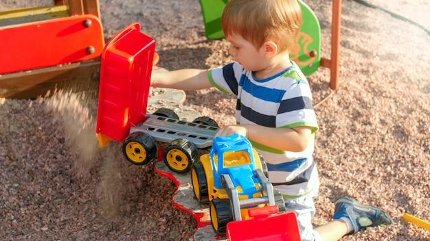 트레일러와 함께 장난감 트럭에 모래를 붓는 쾌활 한 웃는 어린 소년의 초상화. 공원에서 놀이터에서 노는 아이들