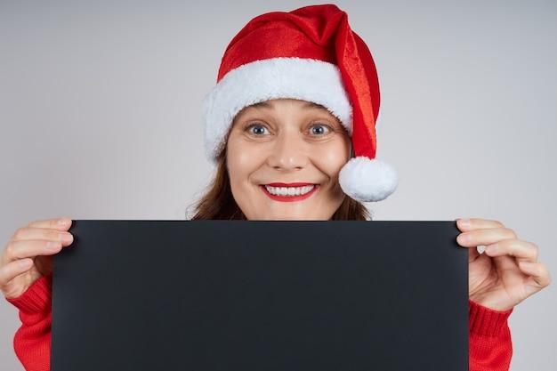 검은 복사본 공간, 광고에 대 한 아이디어를 보여주는 산타 모자에 쾌활 한, 웃는 여자의 초상화.
