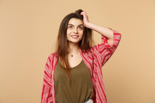パステルベージュの壁の背景に分離された頭に手を置いて、見上げるカジュアルな服を着て陽気な笑顔の若い女性の肖像画。人々の誠実な感情、ライフスタイルのコンセプト。コピースペースをモックアップします。