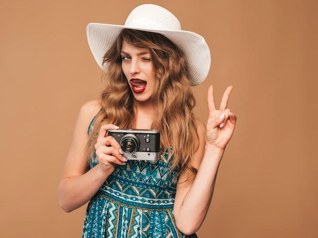 インスピレーションと写真を撮ると夏のドレスを着て陽気な笑顔の若い女性の肖像画。レトロなカメラを保持している女の子。帽子でポーズをとるモデル