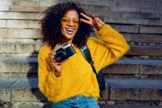 階段の上に座ってレトロなカメラで黒い巻き毛の陽気な学生少女の肖像画