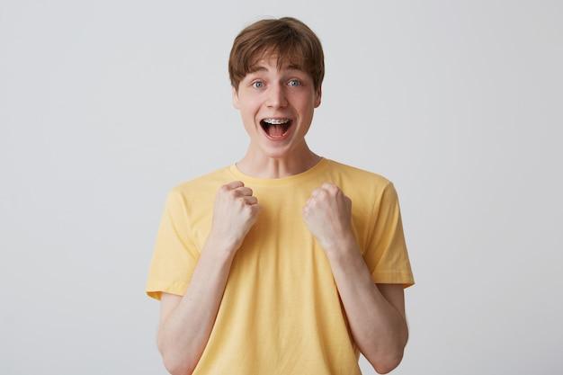歯にブレースと開いた口を持つ陽気な驚きの若い男の肖像画は黄色のtシャツを着て興奮し、白い壁に孤立して叫んでいる