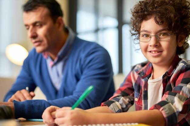 カメラに向かって微笑んで、彼の父と一緒に机に座って、家で宿題をしている眼鏡をかけた陽気な10代のラテン系の少年の肖像画。オンライン教育、ホームスクーリングの概念