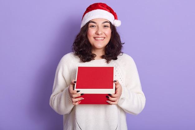 Портрет веселой нежной брюнетки, держащей коробку с подарком в обеих руках