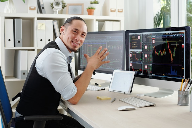 Портрет веселого трейдера, сидящего за своим офисным столом с различными графиками и данными фондового рынка на экране компьютера