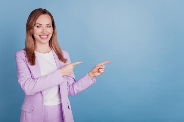 青い背景の上の陽気な女性の直接指の空きスペースの肖像画