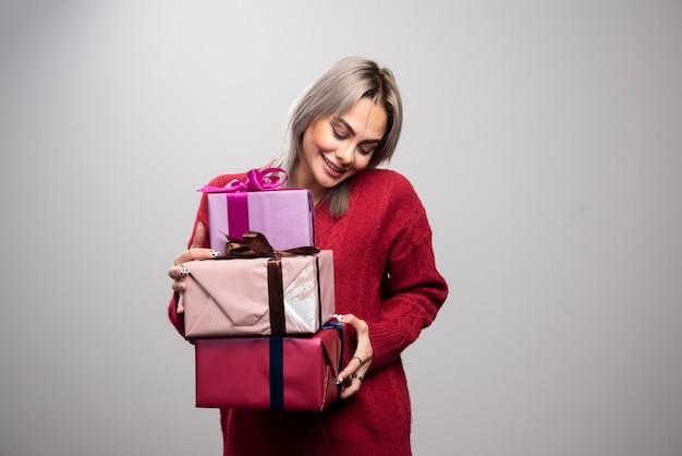 회색 배경에 크리스마스 선물을 들고 있는 쾌활한 여성의 초상화.