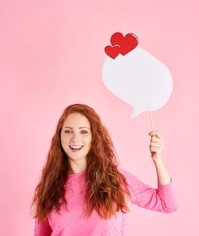Портрет веселой женщины, держащей речевой пузырь в студии выстрел