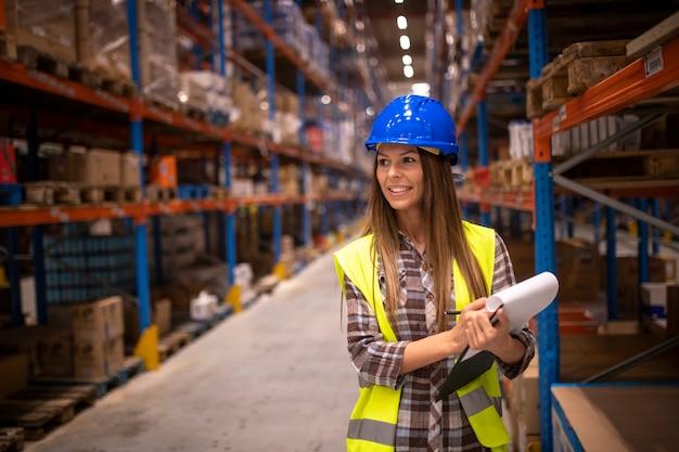 Портрет веселой женщины в защитной форме, проверяющей пакеты и запас продуктов в складском помещении