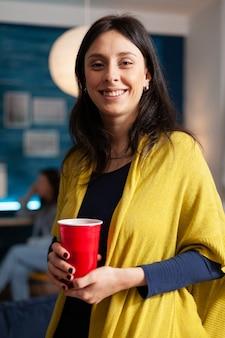 Портрет веселой женщины, смотрящей в камеру, в то время как в фоновом режиме ее друзья весело празднуют день рождения поздно ночью в гостиной. группа многонациональных людей пьет пиво и разговаривает