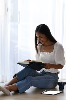Портрет веселой женщины, сидящей на полу в гостиной и читающей книгу.