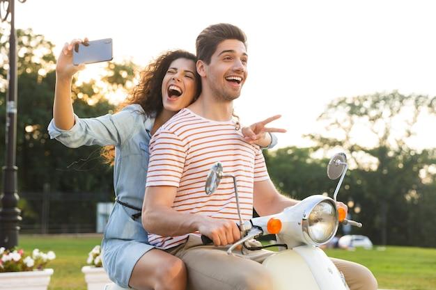 그녀의 남자 친구와 함께 도시 거리를 통해 오토바이를 타고있는 동안 스마트 폰에 셀카를 복용 쾌활한 여자의 초상화