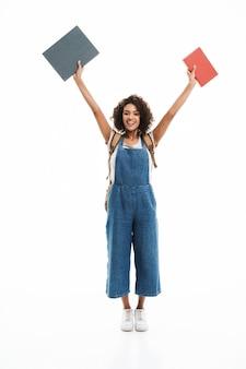 Портрет веселой женщины в рюкзаке, радующейся и поднимающей руки с книгами, изолированными над белой стеной