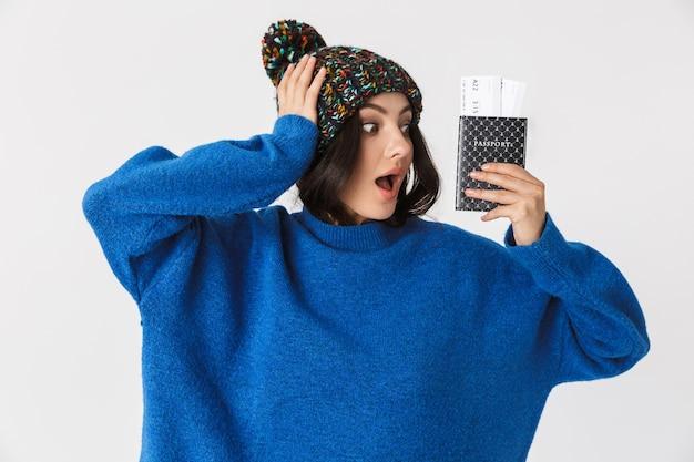 Портрет веселой женщины в зимней шапке, держащей паспорт и проездные билеты стоя, изолированную на белом