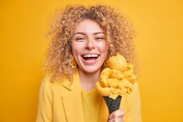Портрет жизнерадостной женщины с вьющимися густыми волосами широко улыбается, наслаждается едой аппетитного мороженого в виде рожков, одетая в желтую одежду, выражает положительные эмоции. концепция летнего образа жизни