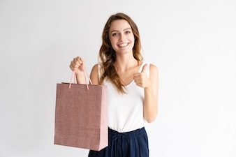 Portrait of cheerful woman with shopping bag showing thumb up.