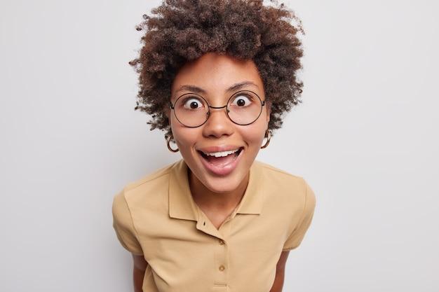 Портрет жизнерадостной молодой афро-американской женщины с вьющимися волосами выглядит изумленно, со счастливым удивленным выражением лица, не может поверить в шокирующую актуальность, одетая небрежно изолирована на белой стене студии