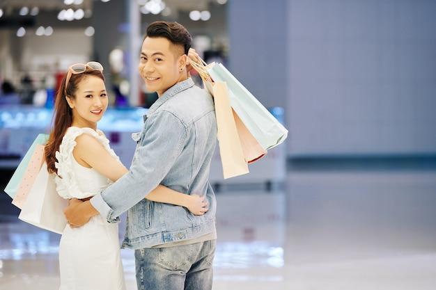 Портрет веселых молодых азиатских мужчин и женщин, держащих сумки для покупок, обнимающихся и оборачивающихся для улыбки