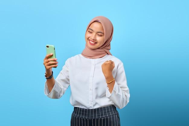 陽気な若いアジアの女性の肖像画は、携帯電話を保持し、挙手で成功を祝う