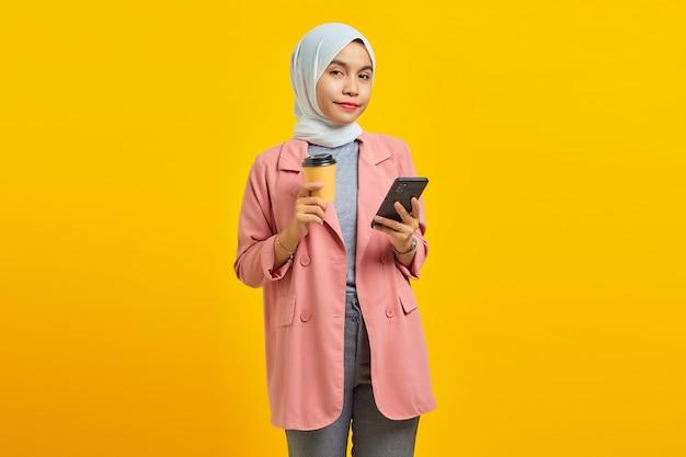 휴대 전화를 들고 파란색 배경에 커피를 들고 쾌활한 젊은 아시아 여성의 초상화