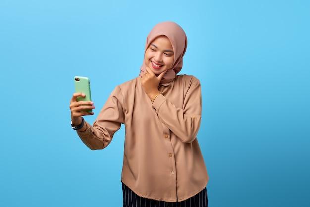 陽気な若いアジアの女性の肖像画は、あごに手で携帯電話を見てください